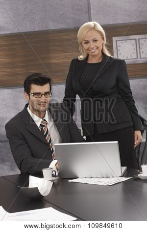 Portrait of elegant businesspeople working together in meetingroom, smiling, looking at camera.