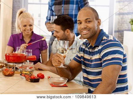 Young man and friends sitting around dinner table, having fondue party, smiling.