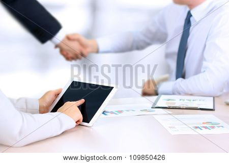 Image Of Business Partners Handshaking Over Business Objects On Workplace. Businesswoman Working Wit