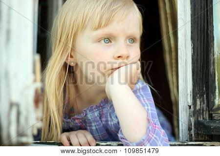 Serious Blond Little Girl Looking Out The Window