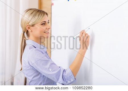 Smiling teacher writing on the whiteboard.
