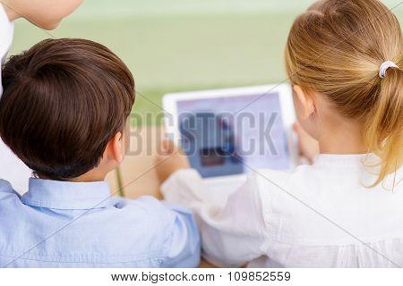 Children using portable tablet.