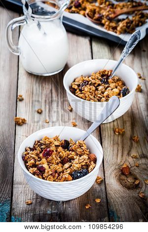 Homemade Granola With Raisins And Nuts In Two White Bowls