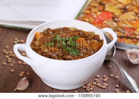 Close up of a bowl of lentil soup garnished with parsley