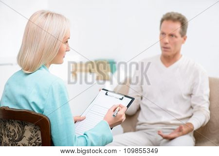 Senior man speaking with psychologist