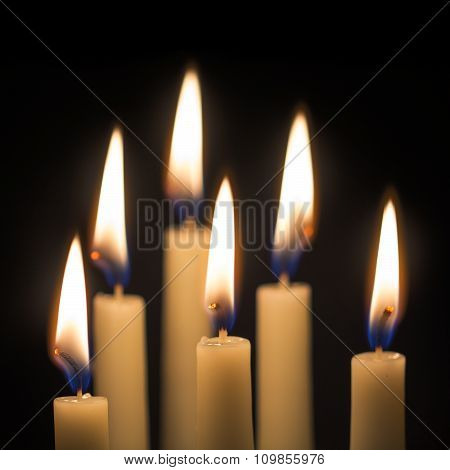 Group Of Six Burning Candles Against Black Background, Selected Focus
