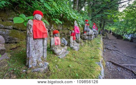 Wide angle of moss covered statues of Jizo in Nikko