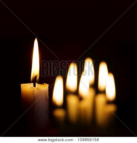 Single Burning Candle And A Group Of Other Candles Blurred In The Background Against Black