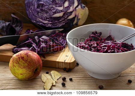 Preparing Red Cabbage For A Festive Dinner With Apple, Onion And Spices On Rustic Wood