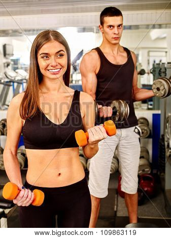 Couple man and woman  working with  dumbbells his body at gym.