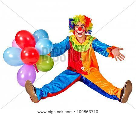 Happy birthday funny clown holding a bunch of balloons and sitting on floor.  Isolated.