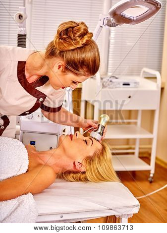 Young woman receiving electroporation  facial therapy at beauty salon.