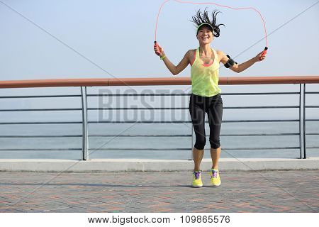 young fitness woman jumping rope seaside