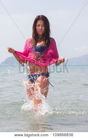 Asian beautiful girl smiling happy on beach vacation enjoying warm sunshine. Mixed race Asian Caucasian pretty model outside with sun in background on Hawaiian tropical beach.