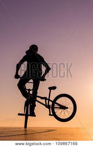 BMX silhouette rider at sunset