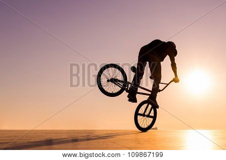 BMX silhouette rider at sunset