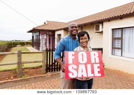beautiful african american couple outside home with for sale sign