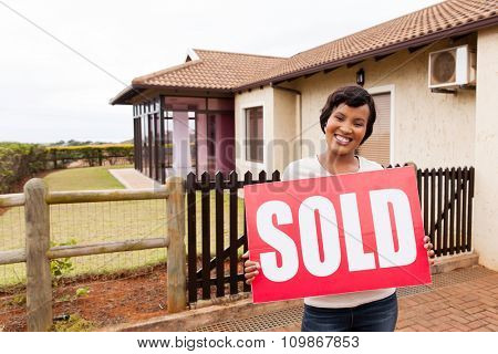 happy african woman holding sold sign in front of house
