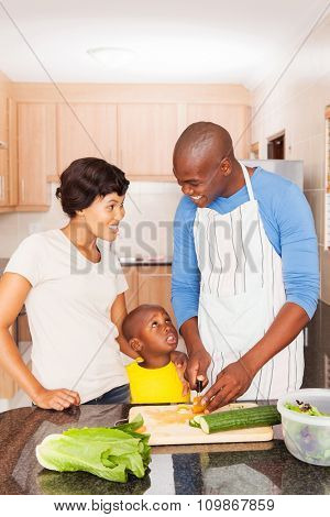 happy african american family of three cooking in home kitchen