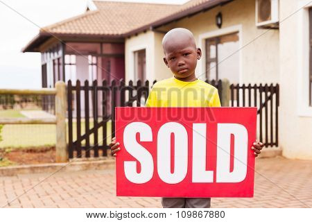 little african boy standing outside the house and holding sold sign