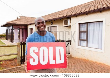 handsome young african man with sold sign in front of his house