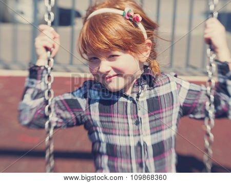 Little redhead girl on the swing looking on the viewer and smiling
