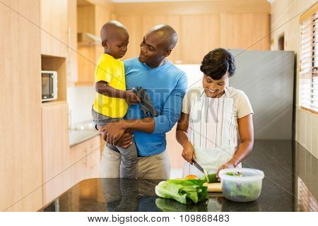 happy young african american family making salad in kitchen