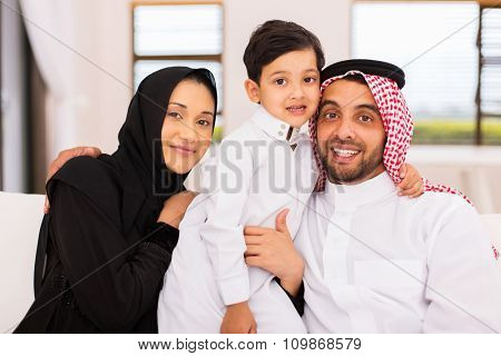 portrait of arabian couple with their son sitting on couch at home