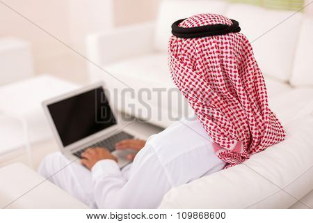 rear view of muslim man sitting on sofa using laptop