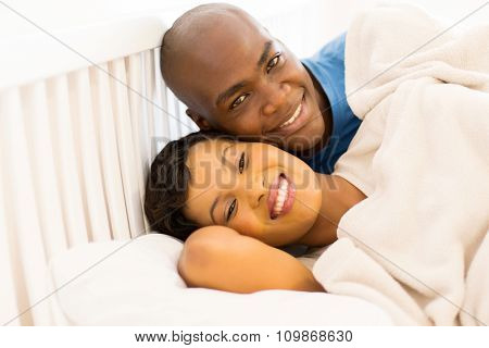 portrait of happy young african couple in bed