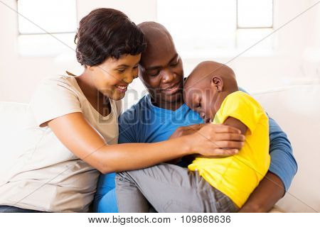 loving young african couple comforting their ill son at home