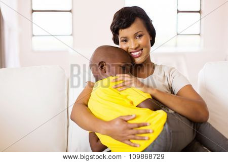 attractive young african woman sitting on couch with her son