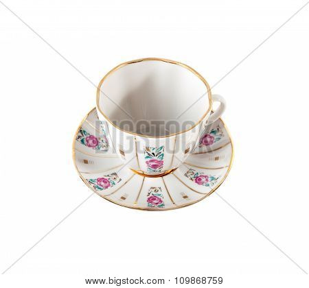 Ceramic teacup and saucer with floral roses ornament in retro isolated over white