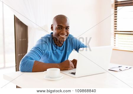 happy african man using laptop computer at home
