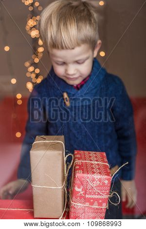 Portrait of adorable kid with gift boxes. Christmas. Birthday