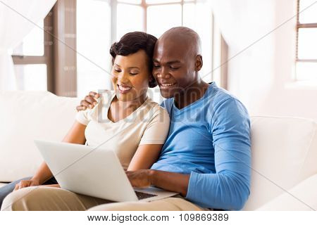 modern young african american couple using laptop computer at home