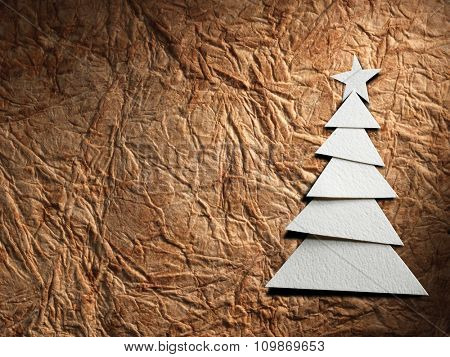 Christmas tree cut out from paper on old paper background