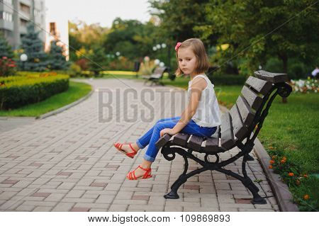 Sad Little Girl Sitting On Bench In Park At The Day Time