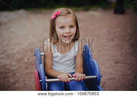 Happy Little Girl Is Swinging