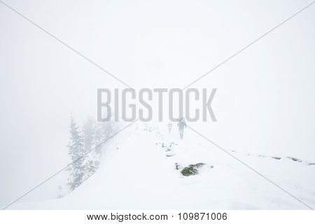 Male and female mountain climbers with huge backpacks and trekking poles having hard hiking trip during winter storm in Austrian Alps