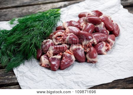 Raw Duck Hearts On Crumpled Paper, Decorated With Dill. On Old Wooden Table.