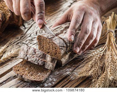 Man's hands cutting bread on the wooden plank.