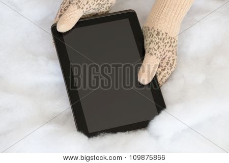 Woman Hands In Light Teal Knitted Mittens Are Holding Modern Tablet Pc On Snow Background.