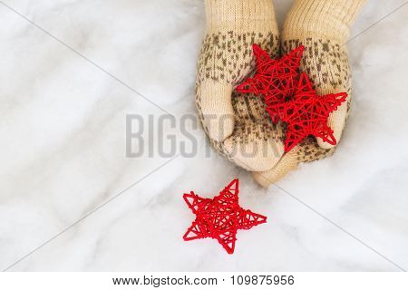 Woman Hands In Light Teal Knitted Mittens Are Holding Red Stars On Snow Background.
