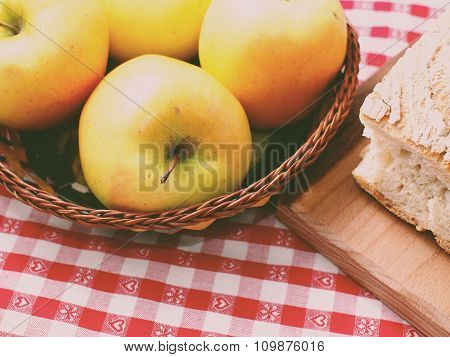 Picnic with bread on wooden cutting board and apples in a basket on red checkered table cloth