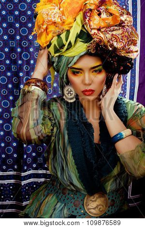 beauty bright woman with creative make up, many shawls on head like cubian, ethno look closeup