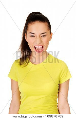 Frustrated and angry teen woman screaming.