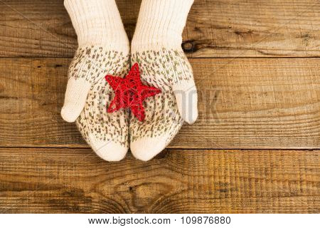 Woman Hands In Light Teal Knitted Mittens Are Holding Red Snowflake On Wooden Background.