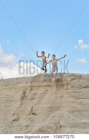 Two boys on a sandy hill