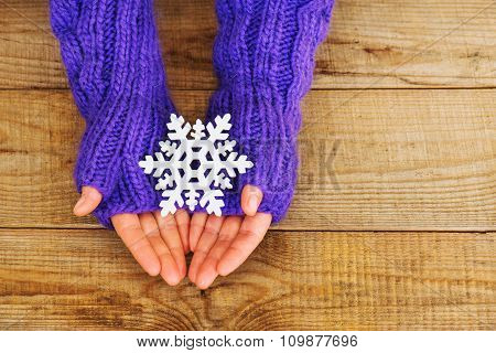 Woman Hands In Light Teal Knitted Mittens Are Holding Snowflake On Wooden Background.